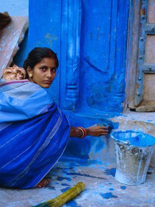 Mujer pintando su casa en la ciudad de Jodhpur
