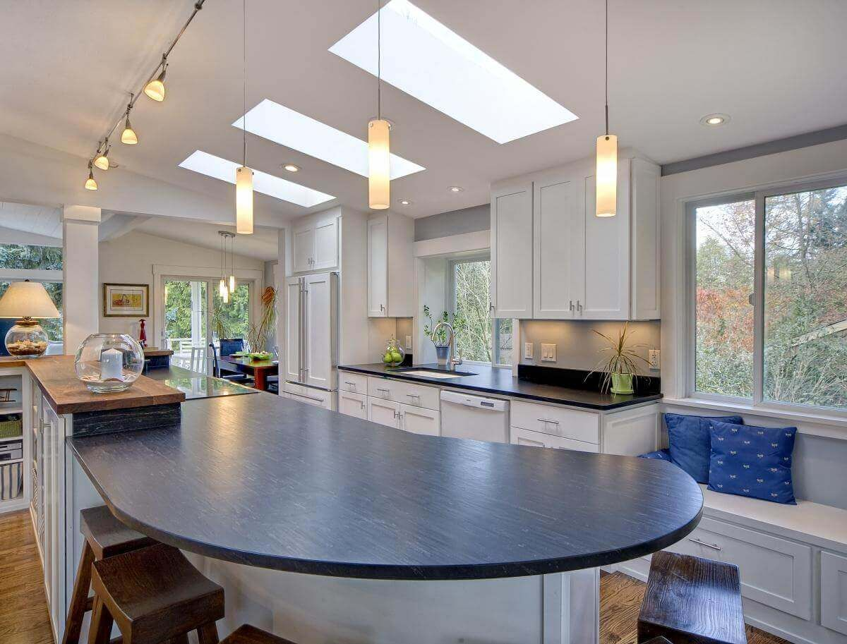 it is easy to see from this angle how much extra light has been brought into the space through the contemporary kitchen ceiling lights and the three big