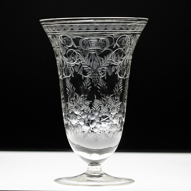 A handsome crystal vase, the trumpet form set on a conical base. The vase is finely engraved with scrolled leaf...