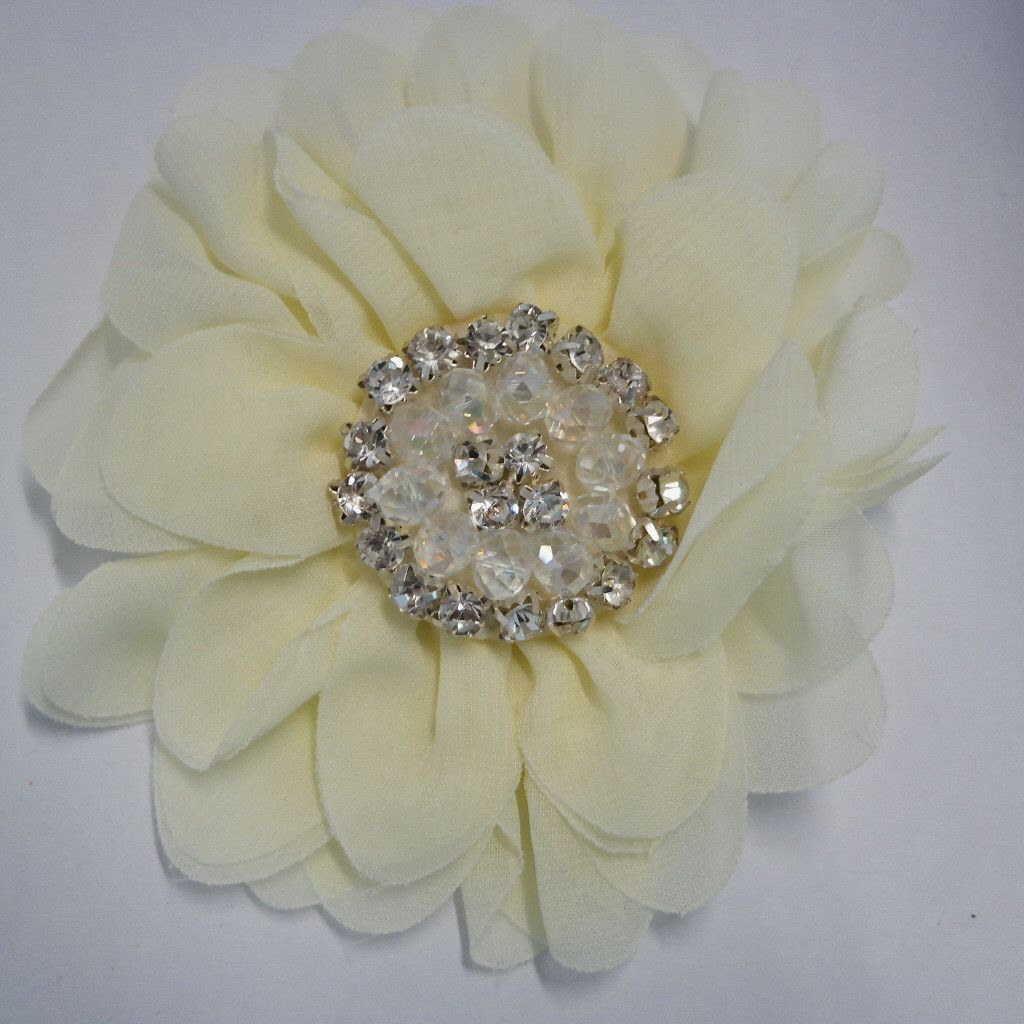 "This shimmering hair flower is perfect for any occasion. It features a 5"" flower made of flowing fabric. Each flower is accentuated with rhinestones and sparkling beads in the center of the flower. Th"