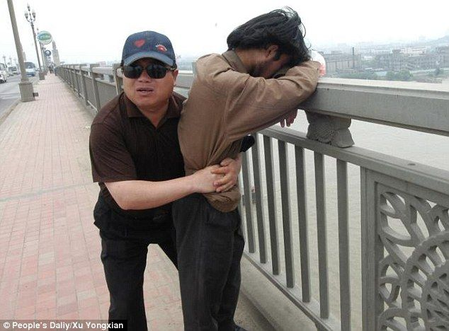 Heroic: Chen Si dedicates his life to preventing suicides on the Nanjing Yangtze River Bridge. Above, Chen tried to save a man on May 16, 2004