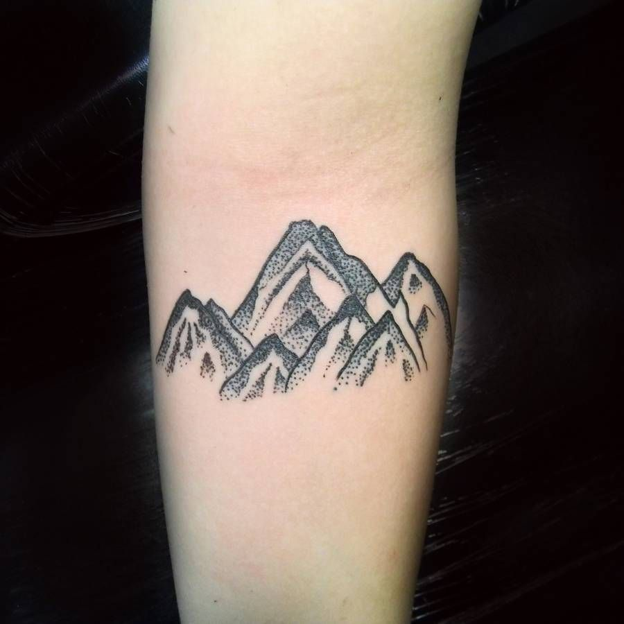 Dotwork style mountains tattoo on the inner forearm