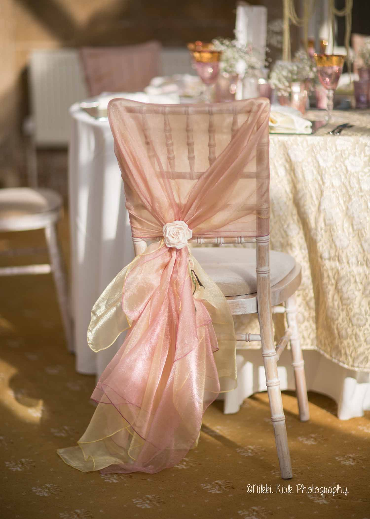A Limewash Chiavari Chair With A Hand Tied Dusky Pink And Gold Organza Sash With Rose Tieback