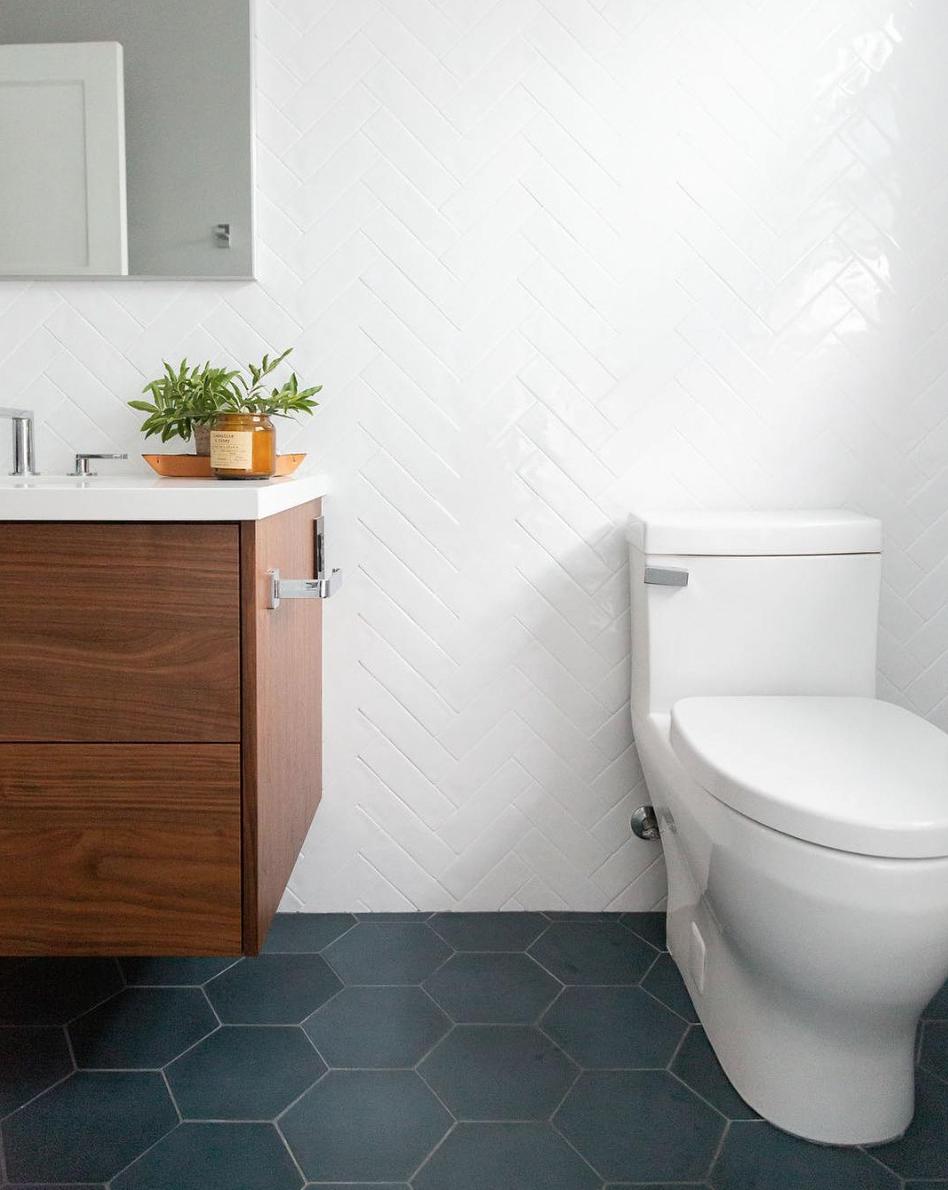 large grey hex floor tile and white herringbone wall tile