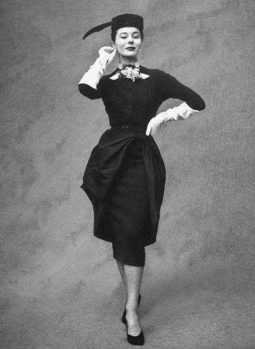 BALMAIN A 1951 design by Balmain, featuring a tucked apron, elegant lines, and chunky baubles with gloves. The designer was known for catering to the needs of wealthy, aristocratic clientele.