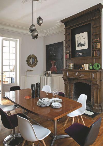 Une cheminée en bois imposante fait face à une table style années 60 dans la salle à manger. Plus de photos sur Côté Maison http://petitlien.fr/8293