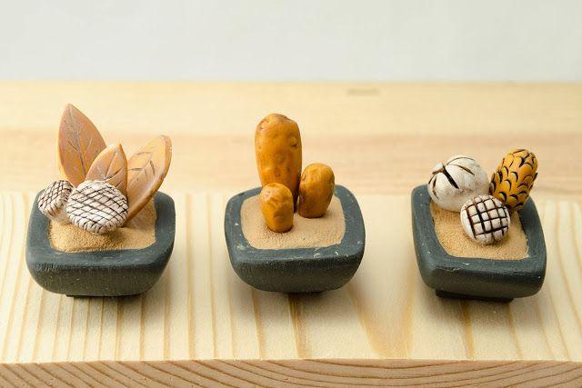 tres macetas en miniatura sobre base de madera