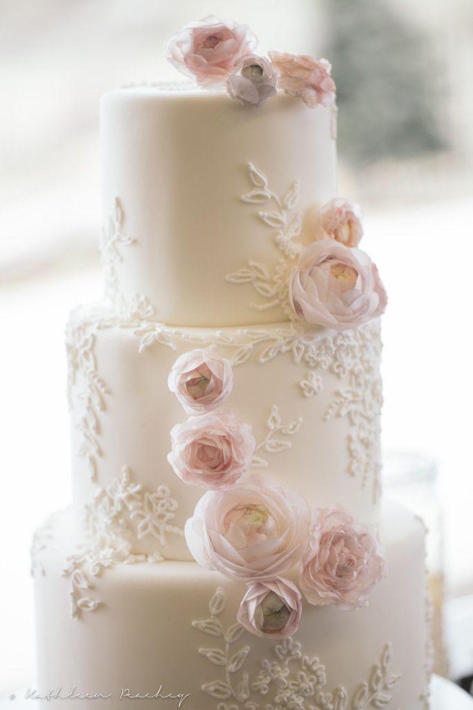 Elegante torta nuziale a piani con fiori rosa pastello