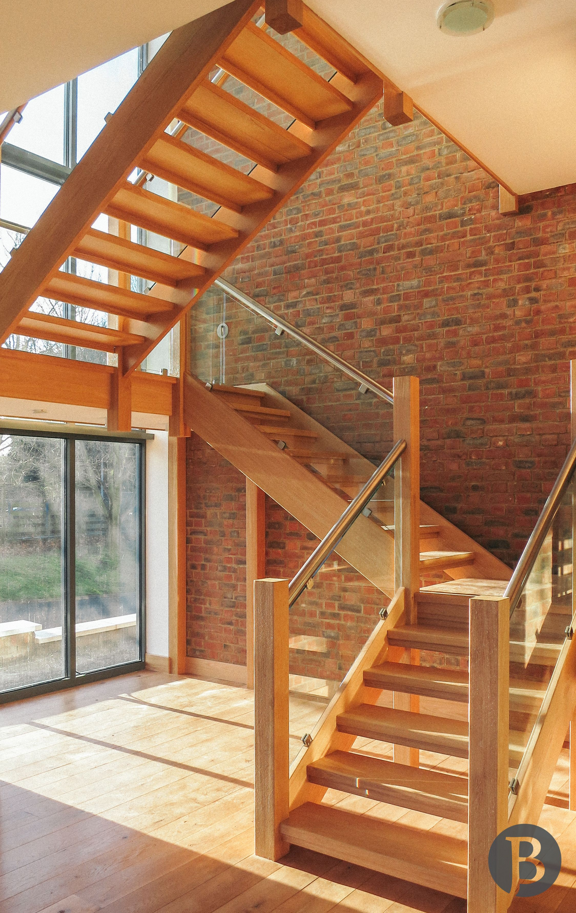A Statement Half Landing Open Tread Staircase With Glass Stairs