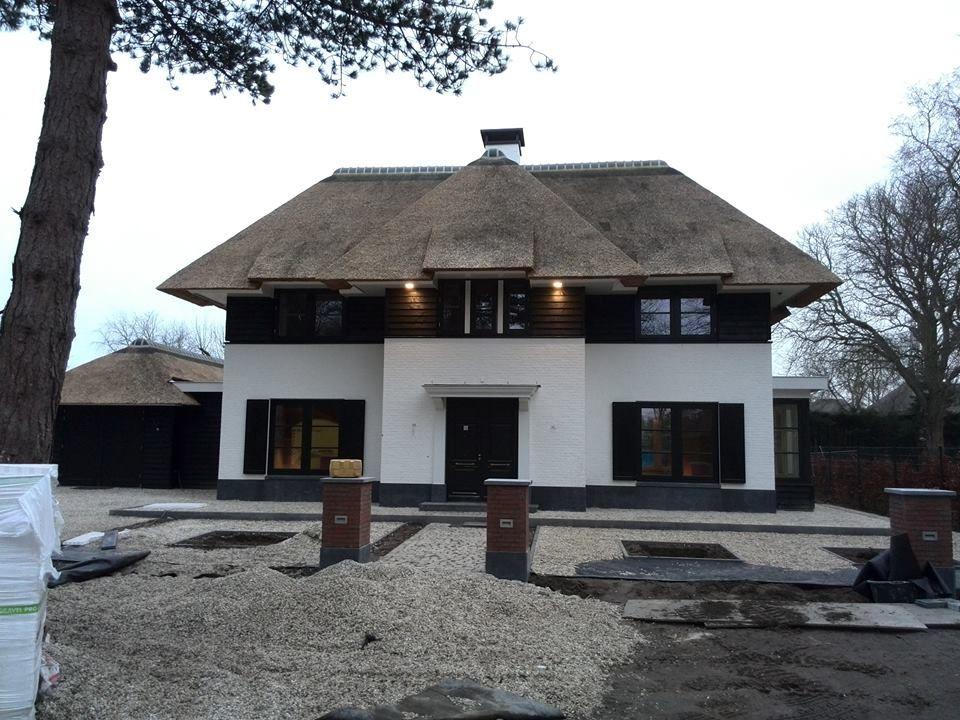 gestuct huis met zwarte potdeksel planken rieten dak