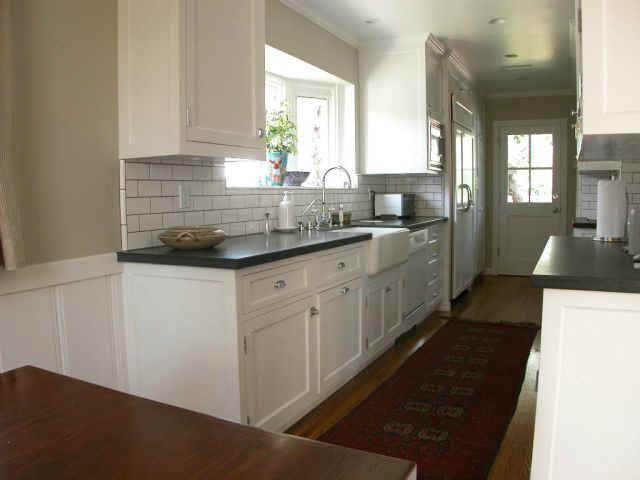 Galley kitchen with white cabinets/backslpash. Black ...