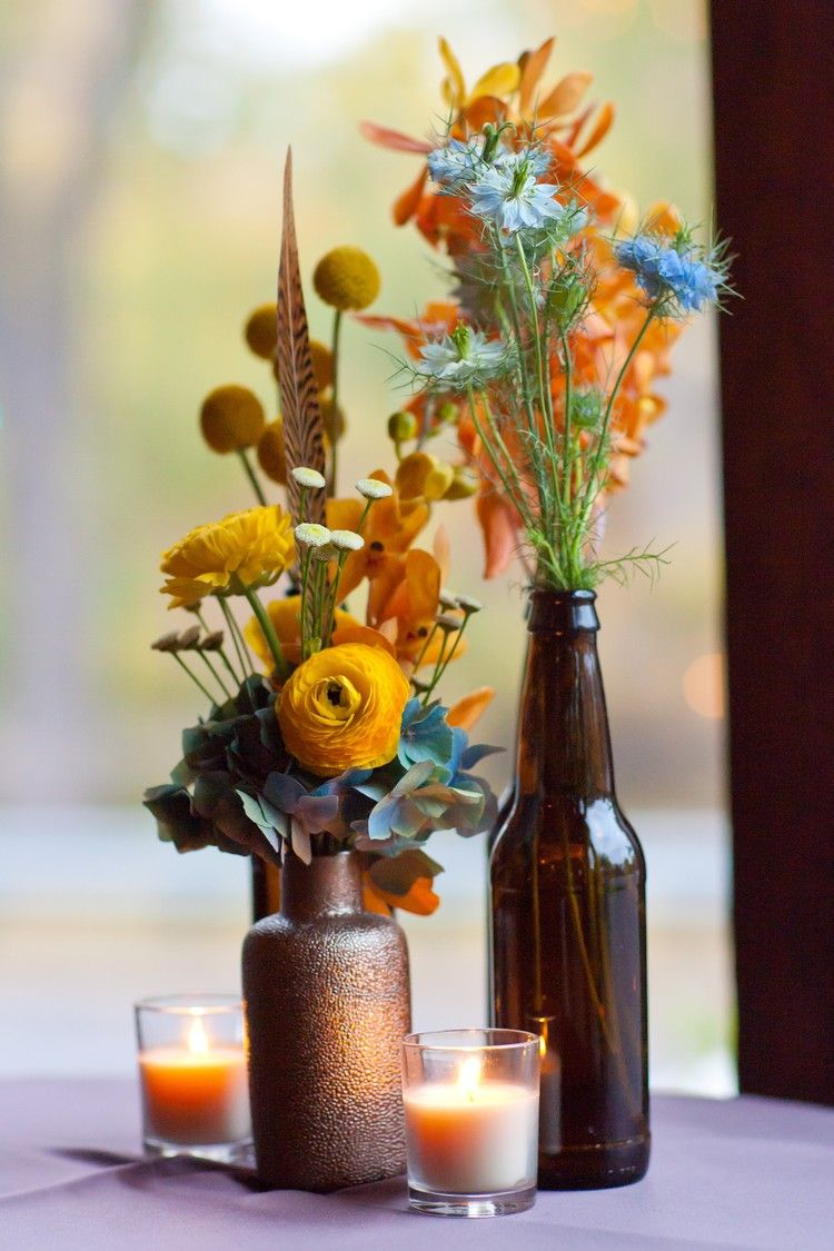 Rustic wedding flowers with pheasant feathers and beer bottle vases