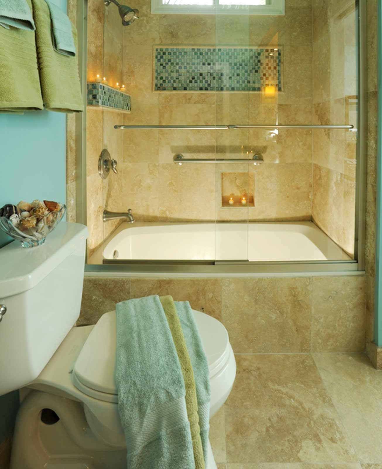 A travertine tile shower with glass mosaic accent is the highlight ...