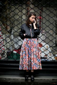 A floral midi skirt, bomber jacket, and flats.