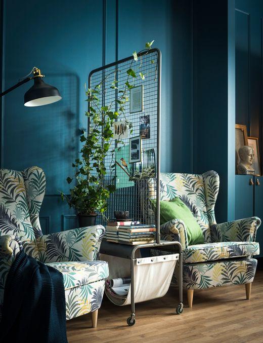 Tussen twee fauteuils staat een kamerverdeler met een for Interieur tijdschriften nederland