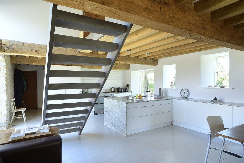 O2i Design's architects revived this characterful period farm outbuilding and overhauled this dilapidated period barn on the Somerset Levels. The result is a contemporary home with exposed wooden trusses and stonework in a light modern and interior. #kitchen #openplanliving #beams #barnconversion © O2i Design Limited.
