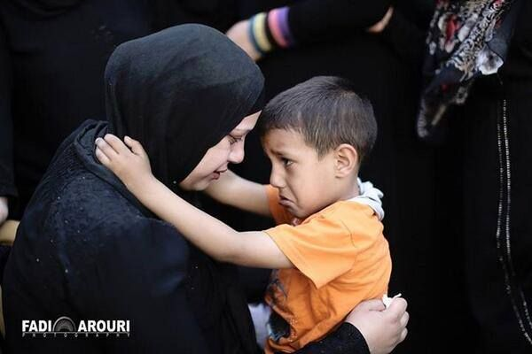 Palestinian boy trying to comfort his Mom hours after israel murdered his father. He is the Man of the family now