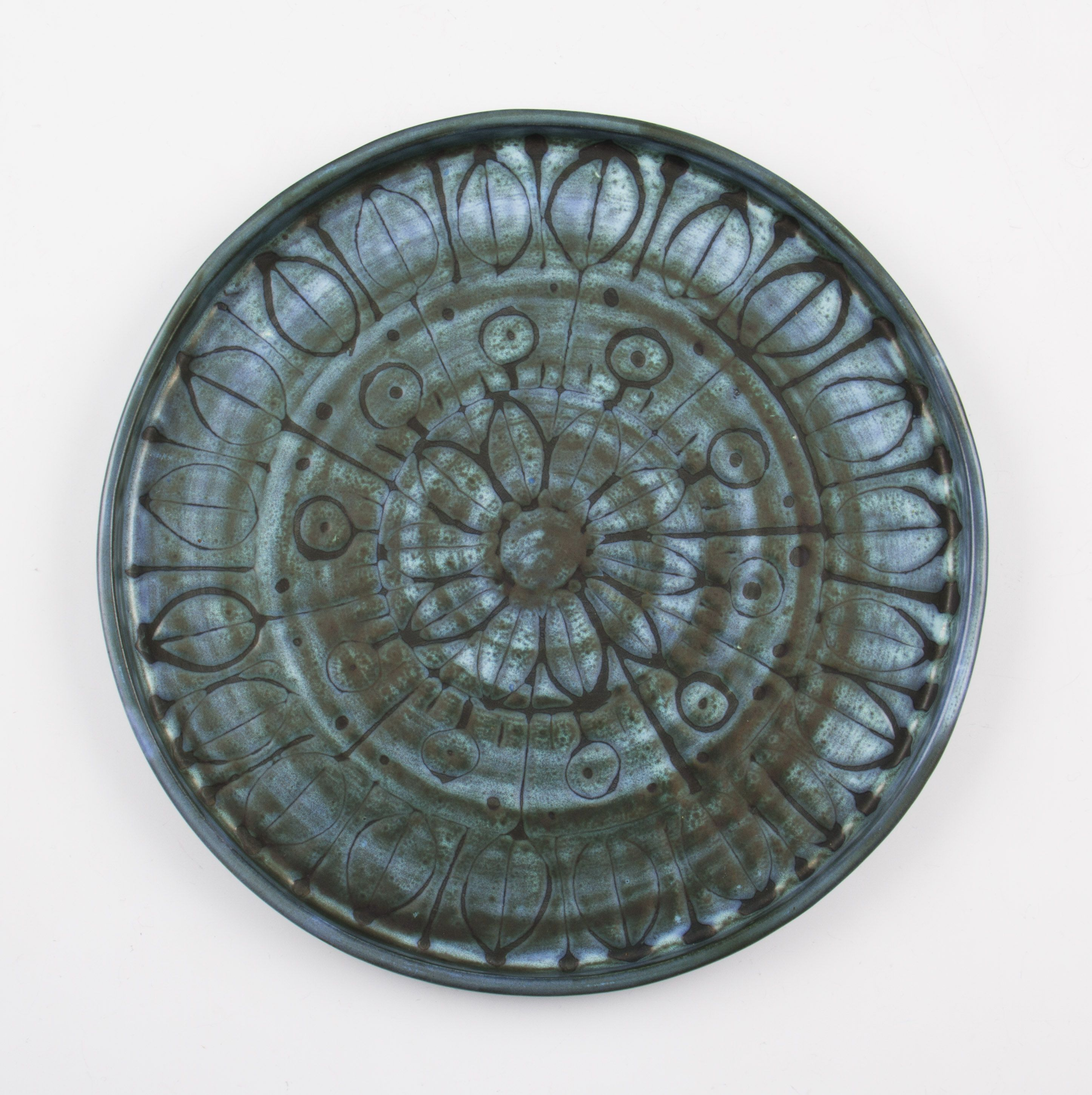 A Troika studio pottery circular plate having stylised leaf