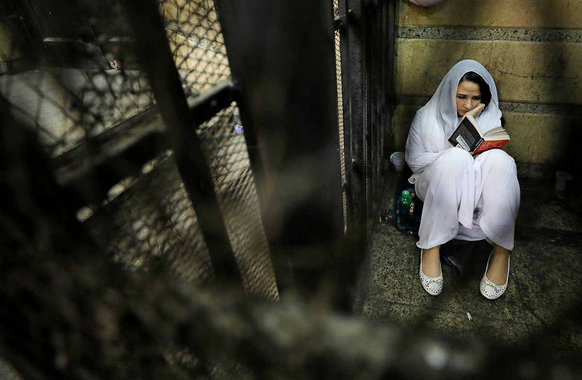 Aya Hijazi, founder of Belady, an NGO that promotes a better life for street children, reads a book inside a holding cell at a courthouse in Cairo on March 23 before her trial on charges of human trafficking. She was acquitted and returned to the US on April 20.