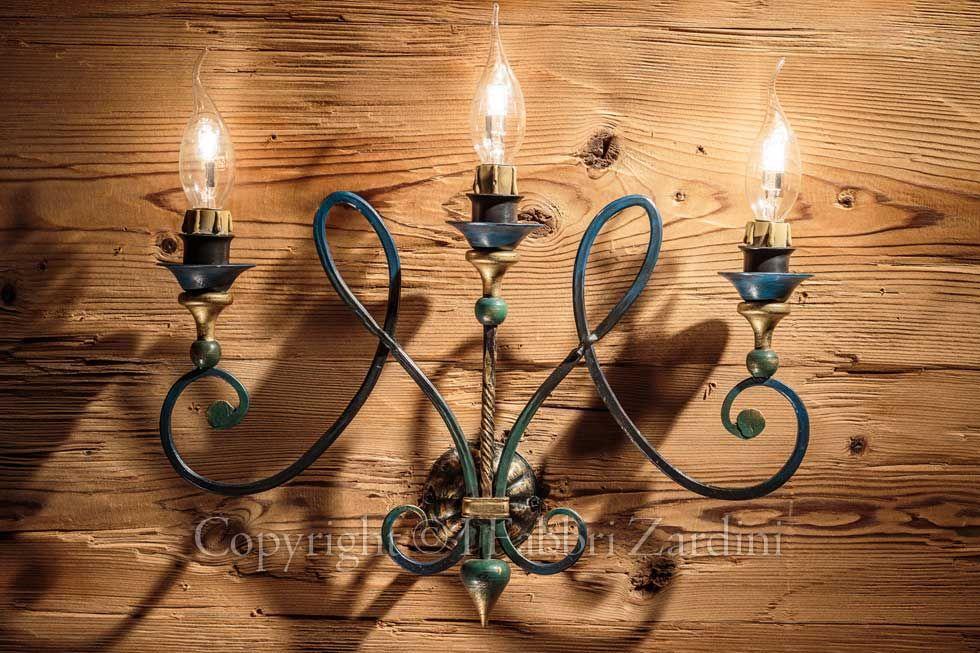 Applique a luci con volute in ferro battuto decorato a mano