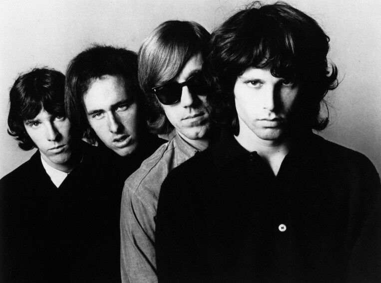 The Doors , from left to right , John Densmore(drums) , Robby Krieger (guitar) , Ray Manzarek (keyboard) , Jim Morrison(lead vocals)