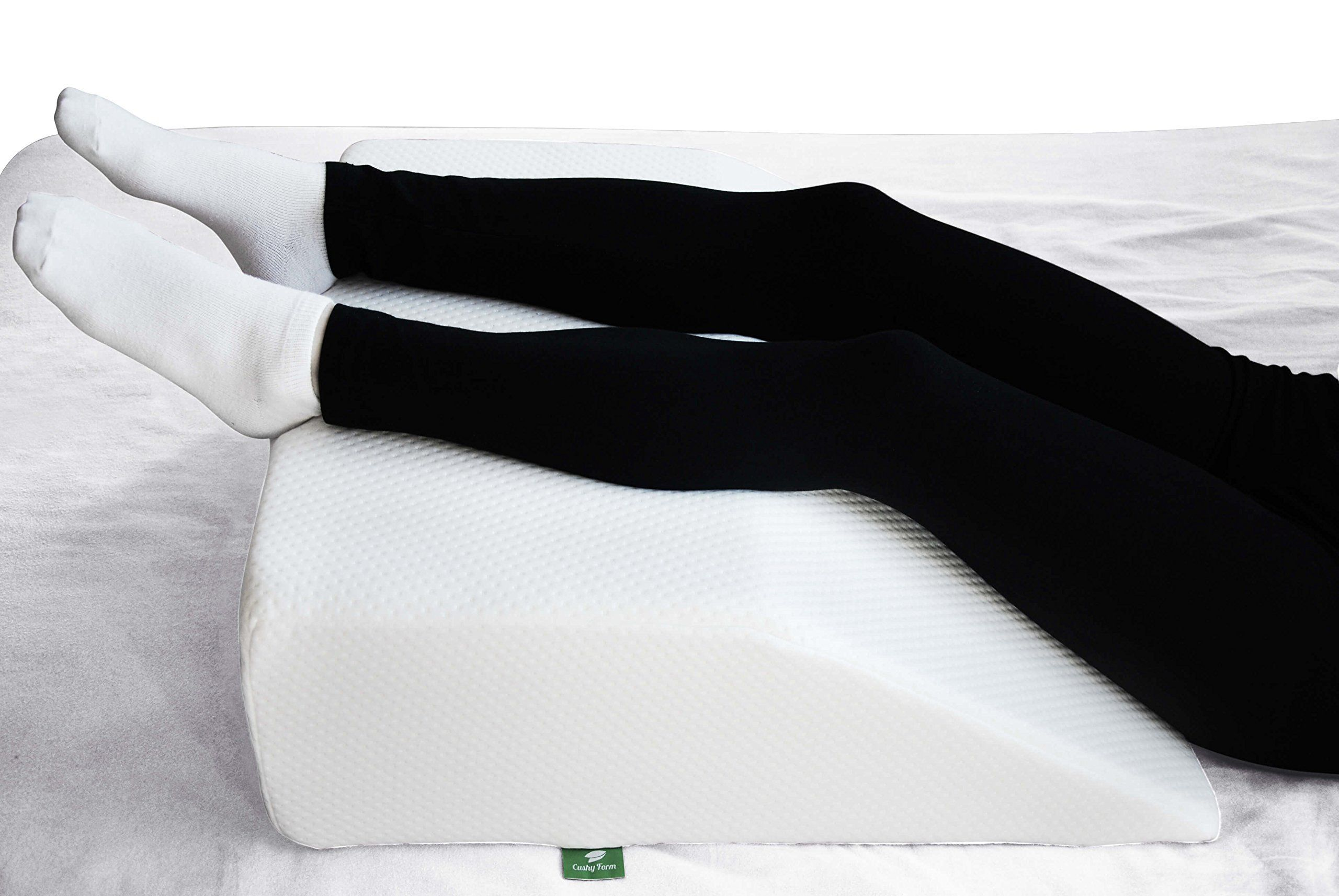 Legs wearing black leggings and white socks resting on a leg rest pillow