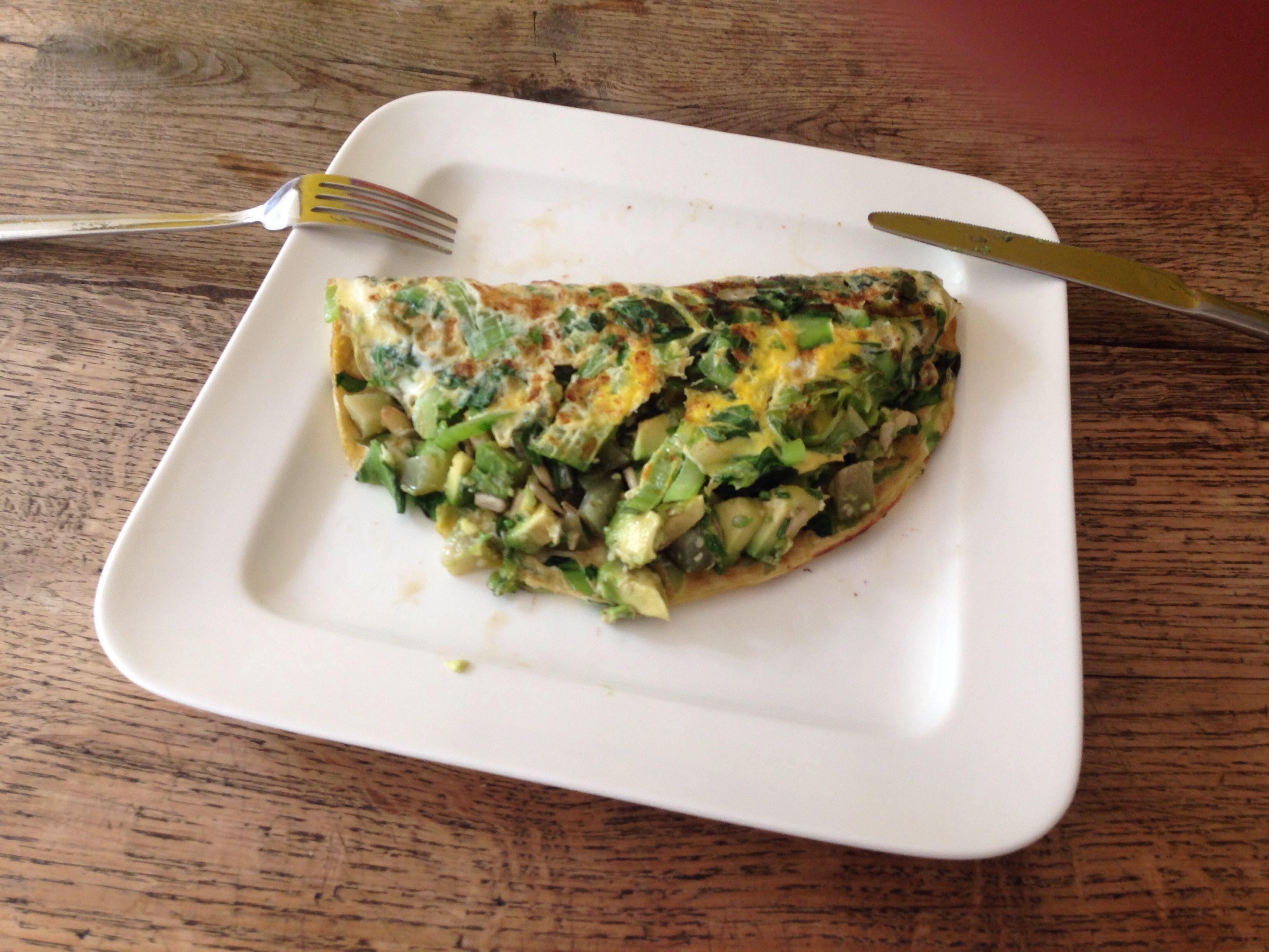 Omelet met paksoi en romeinsla. Met een avocado, augurk, zonnebloempitten, hennepzaad en bieslook vulling.