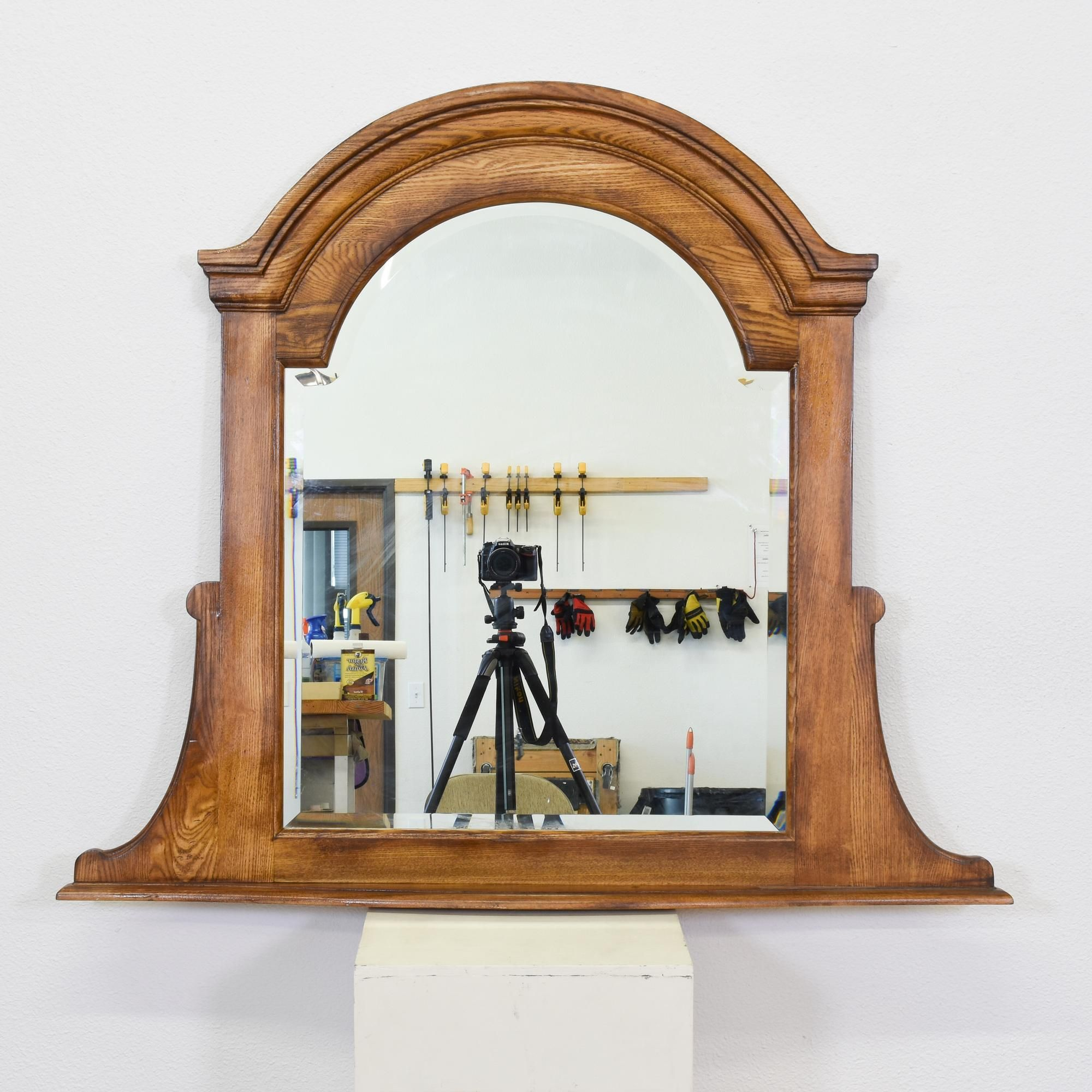 This mantel mirror is featured in a solid wood with a glossy oak