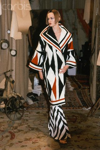 * John Galliano for Dior Spring/Summer 1999 Dior's Russian Constructivist inspired ready-to-wear collection, Model holding closed black, red and white geometric print robe with wide collar and arms, over black and white zig-zag skirt ca. 1999 © Guy Marineau