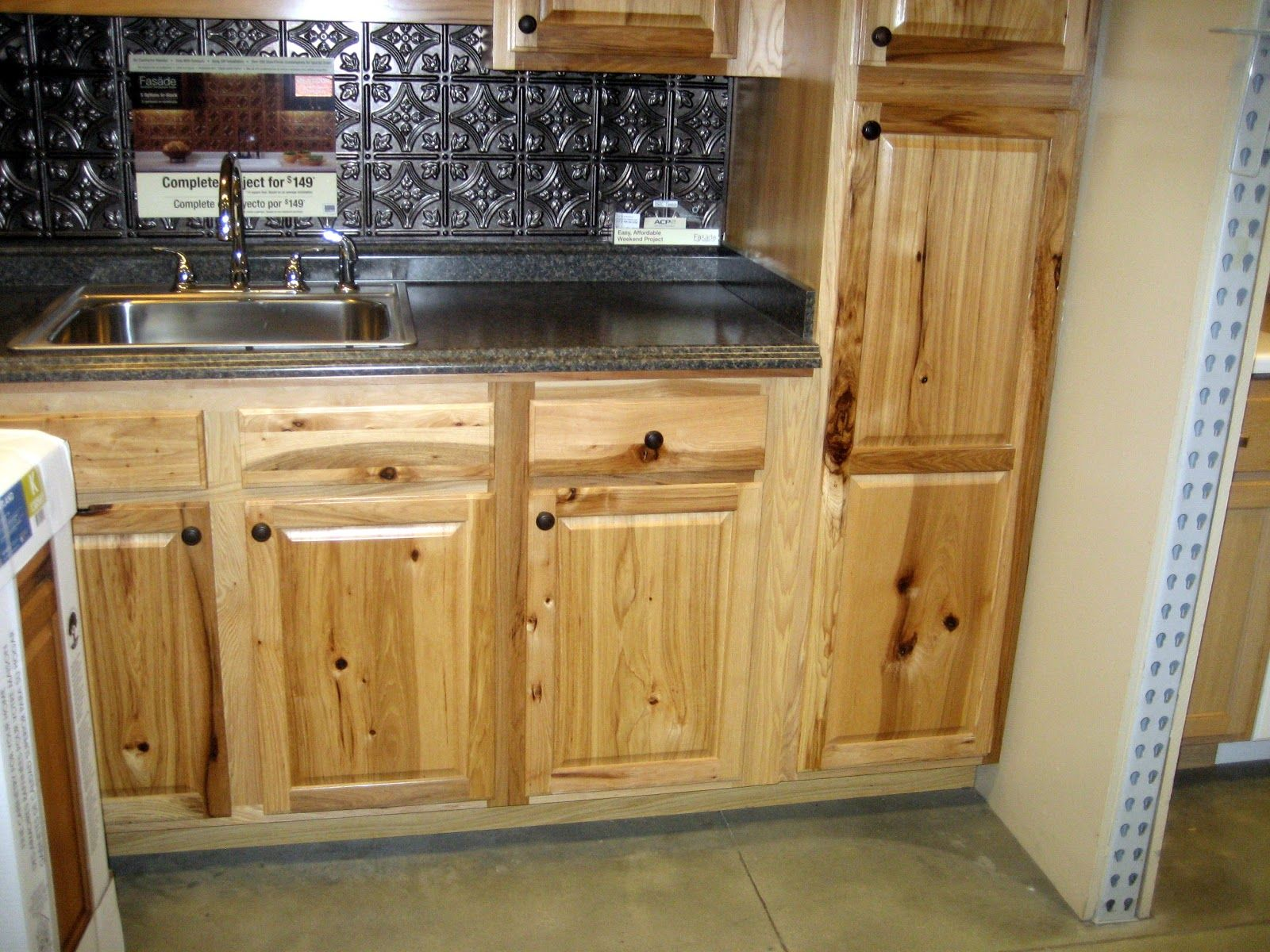 rustic hickory cabinets with black countertop and chrome metal