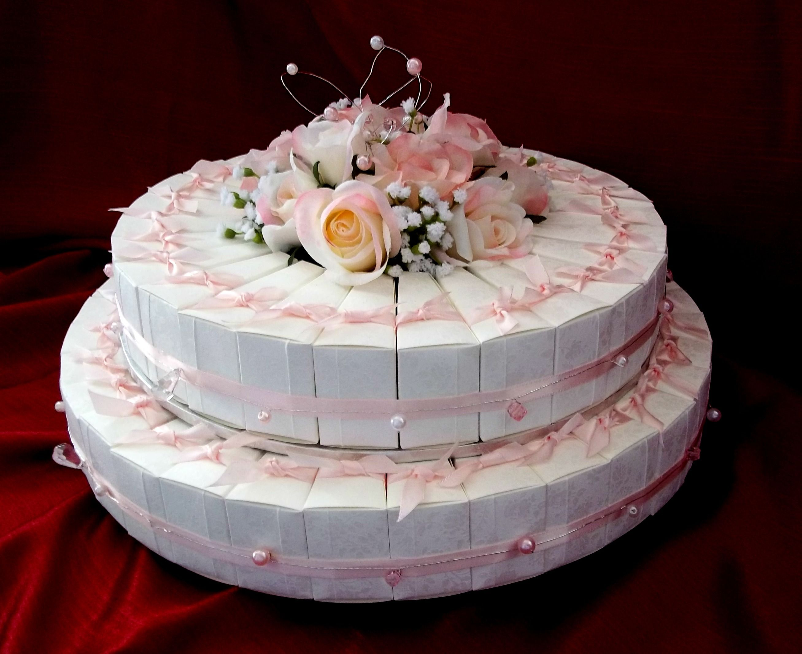This wedding cake consists of 60 - 2 piece boxes of chocolates. finished with a Vass Blush ribbon, silk flowers and just a touch of bling.
