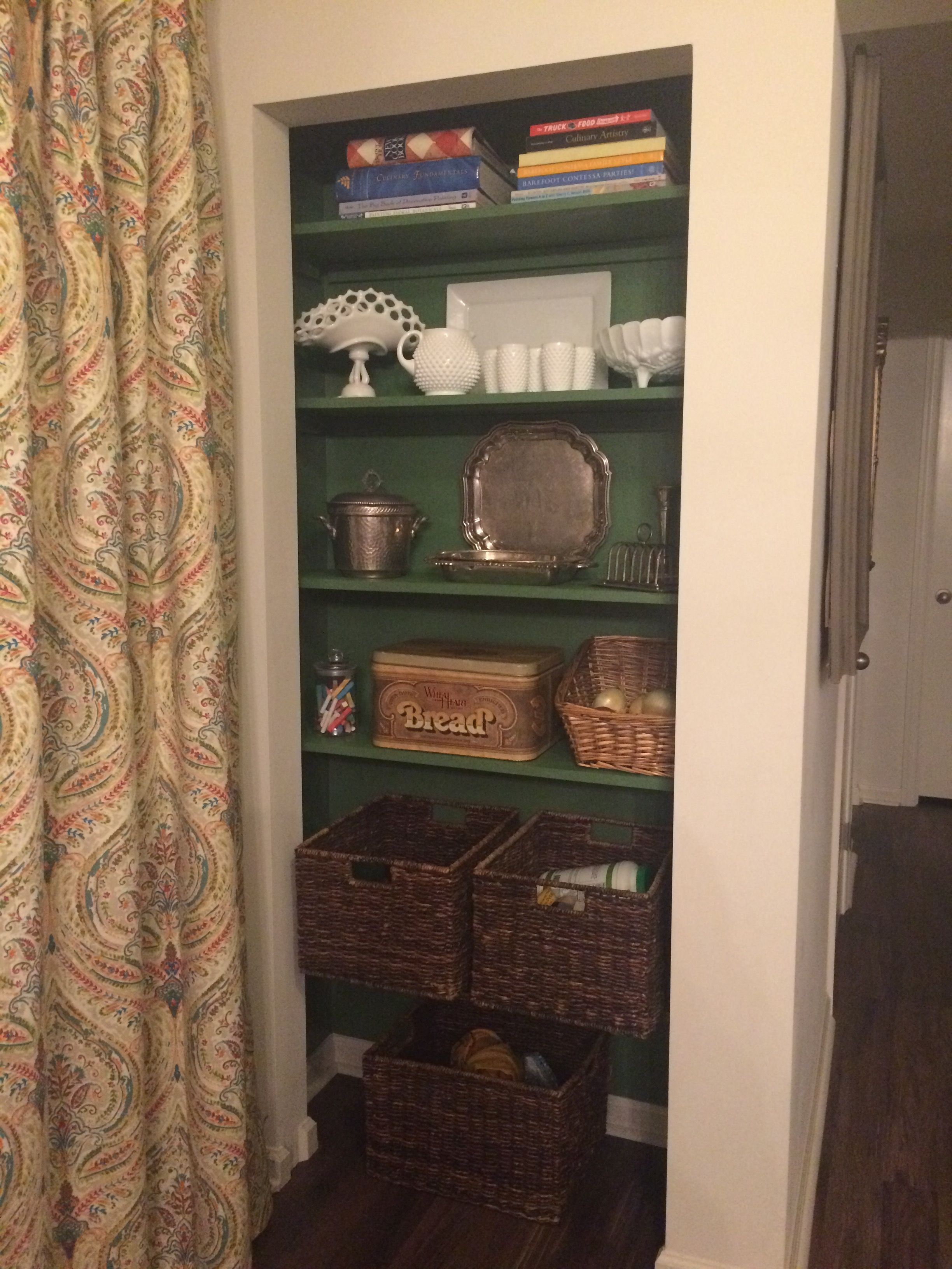 Former tiny pantry is now a built in. Removed bi-fold doors & wire shelving. Added wood shelving & paint.