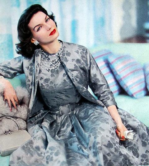 ~Joanna McCormick, 1957. 1950s fashion dress brocade demask jacquard silver blue cocktail evening dinner jacket color photo print ad model magazine 50s floral~