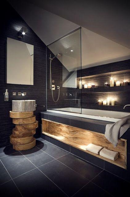 Photo of Viel indirekte Beleuchtung im Badezimmer mit schwarzen Fliesen und Holz.