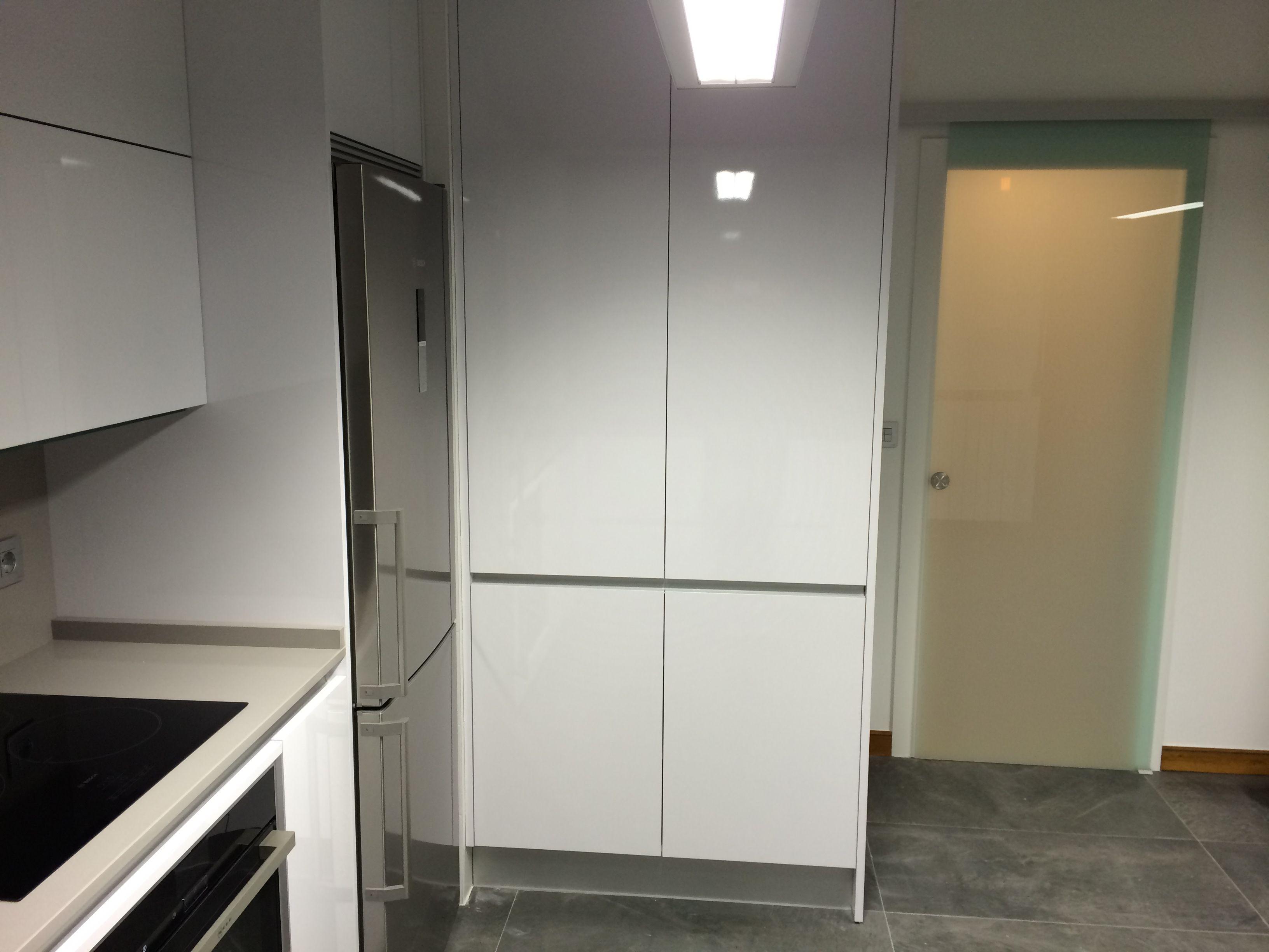 Cocina moderna con muebles blancos y puerta corredera de cristal ...