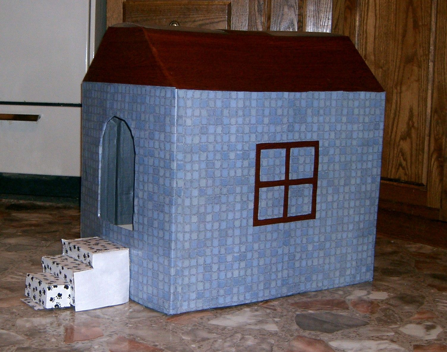 A cat litter box cover made from cardboard and contact