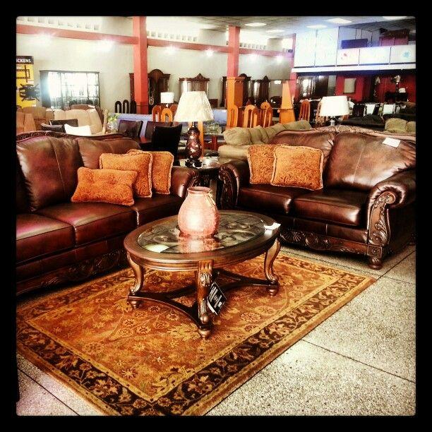 Juego de muebles de Ashley Furniture en piel y madera, acompañado por cojines, mesas, lámparas y alfombra de la misma marca