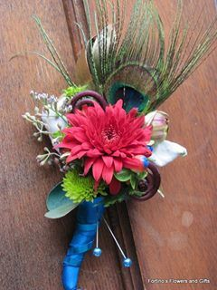 Boutonniere for wedding.  Dahlia, green button, fern curls, peacock feather and more.