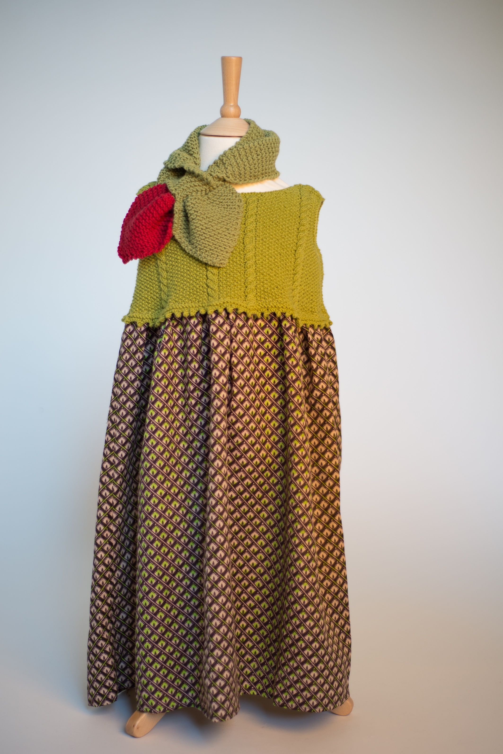 This hand knitted green merino and cotton bodice is attached to a limited edition African tribal print skirt and teamed with the Ruby's signature 1940's Ascot scarf.