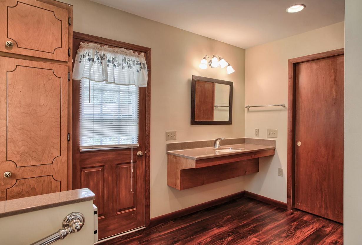 Bathroom vanity with dark wood and tan countertop ...
