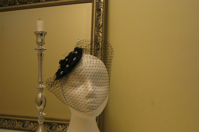 Ohlala by mad-hatter.    Elegant little hat and veil to up your outfit.  Black straw base completely covered with hand-made black fabric flowers, topped with pearl glass beads. With bird cage veil.