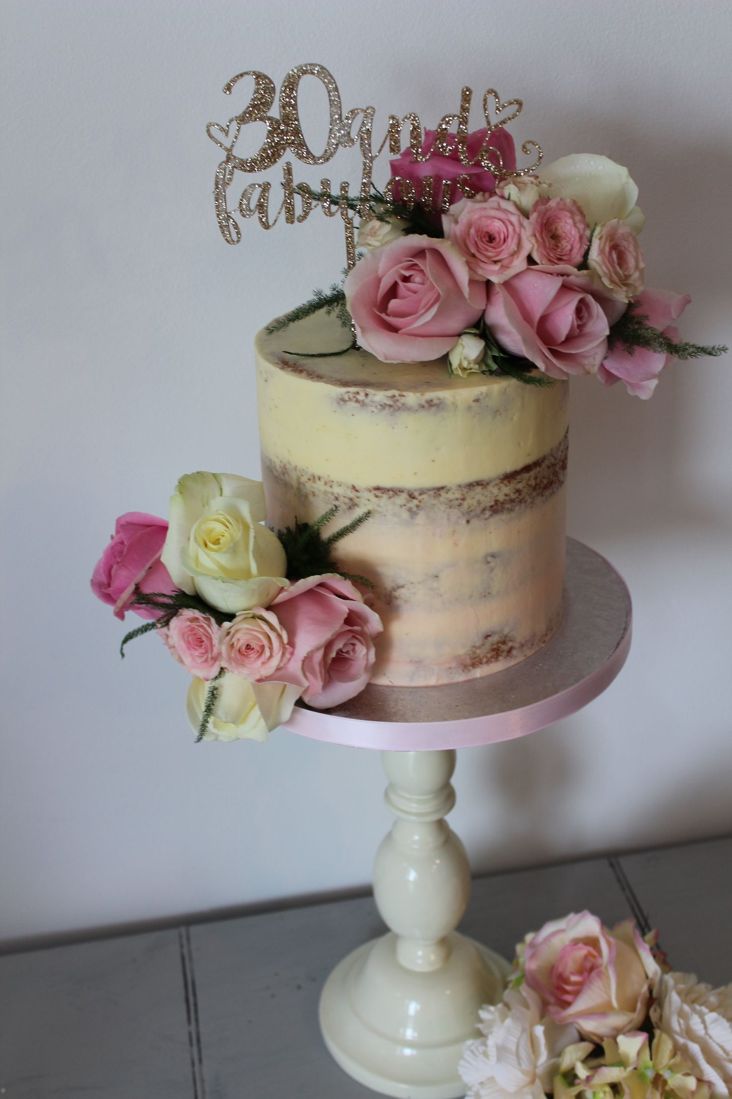 Semi naked 30th birthday cake draped with beautiful fresh flowers