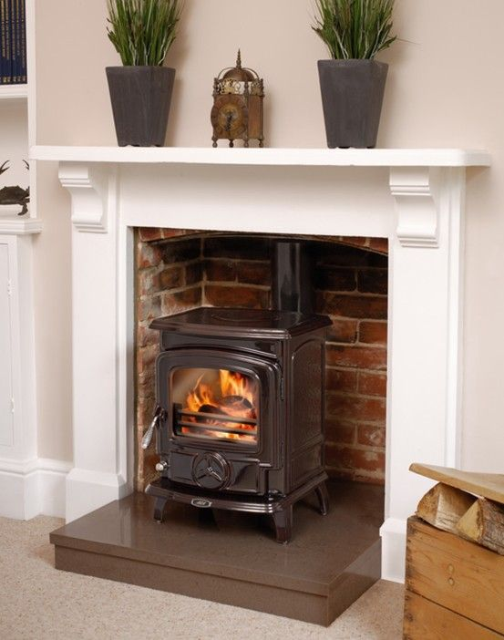 Another Stove With Exposed Brick And A White Mantle Piece
