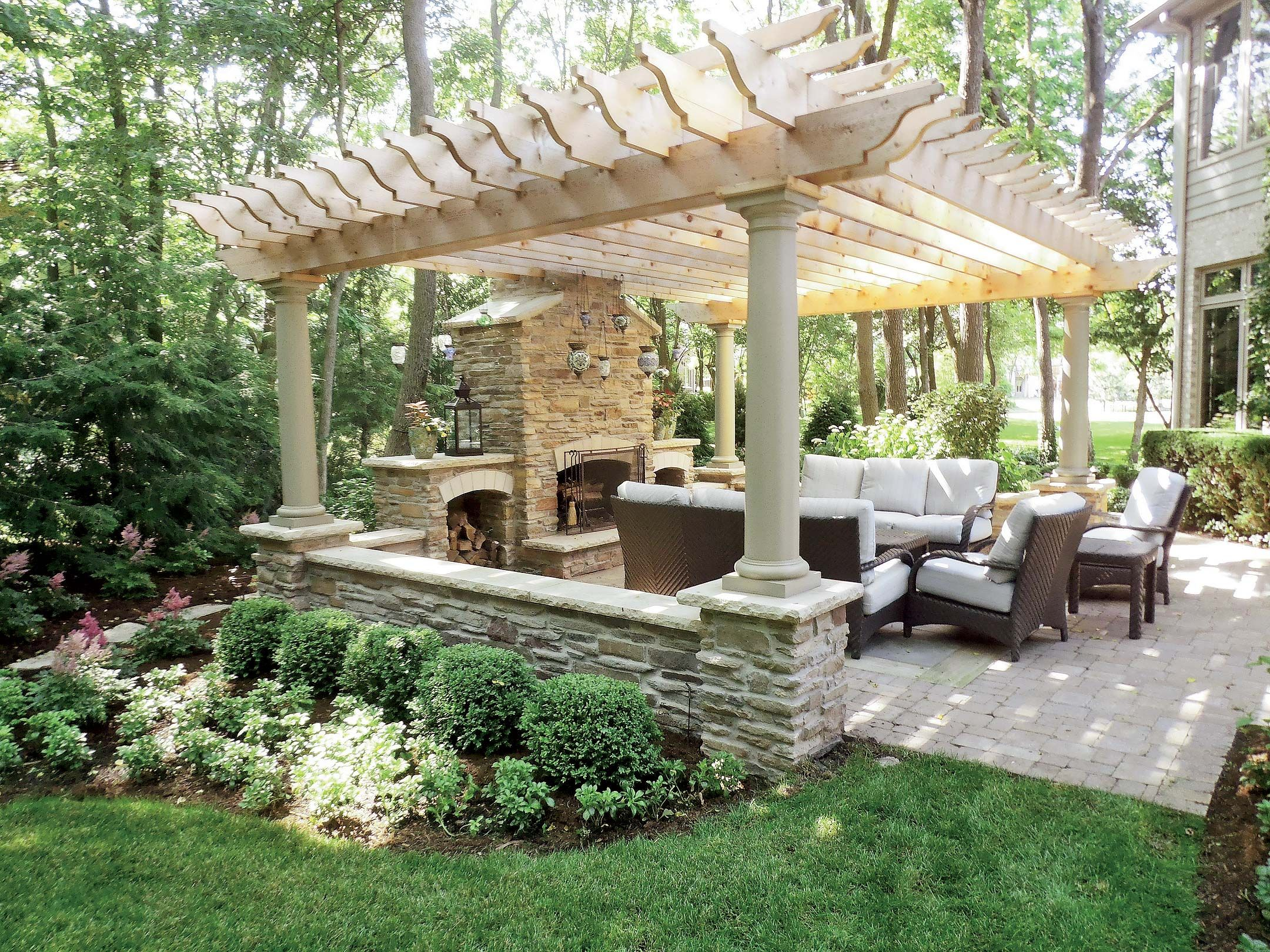 Stonework accents this pergola for an outdoor seating area for Porch and patio designs