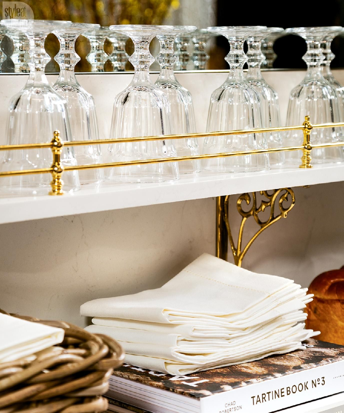 brass-railed shelf for glasses and brass rods for hanging everyday pots, pans and dishcloths, lend an air of a fashionable French bistro.