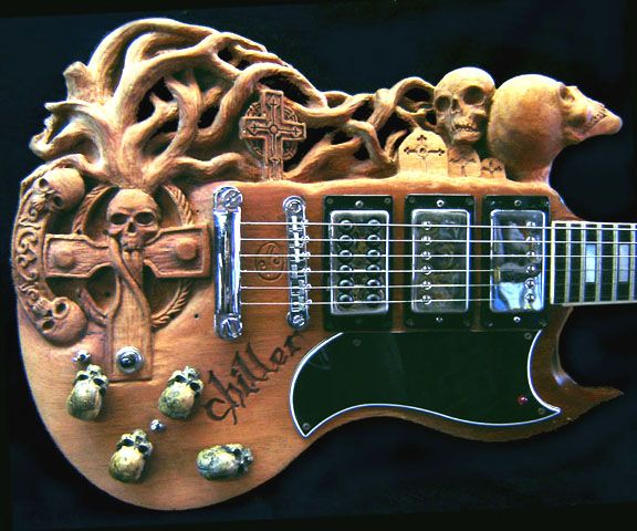 """Commissioned by David Ledogar of Massapequa, NY.  Started out as a white 1975 Gibson SG Standard - David wanted his SG to represent the Goth style. He wanted Skulls, tombstones, crosses and a big scary tree. We sent designs back & forth by email until we came up with the """"Chiller"""". Dave sent along the cool skull pot knobs. Nice touch! The finish is a dark walnut oil stain."""
