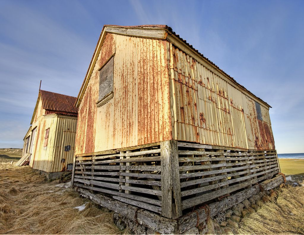 These old decrepit and stained sheds stuck out in the windy and cold tundra of western Iceland. Asmundur and I stopped for a few shots while he told me about a bunch of scary Icelandic ghost stories, all of which seemed to involve a huge amount of alcohol.    - Photo from #treyratcliff Trey Ratcliff at http://www.StuckInCustoms.com    - Iceland