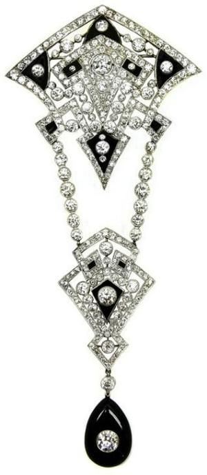 Early Art Deco openwork diamond and onyx corsage brooch, c.1920, of geometric design formed by two graduated kite motifs, millegrain set with lines of diamonds and inset with onyx sections, the smaller kite hung below on two detachable lines of articulated collet diamonds, the whole suspending a polished pear shaped onyx inset with a round brilliant cut diamond. by desiree