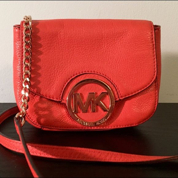 Michael Kors Orange Crossbody Genuine leather, pop-of-color crossbody with a back pocket and inner pocket. Gold MK emblem has some scuffs, overall condition is good. MICHAEL Michael Kors Bags Crossbody Bags
