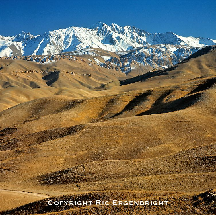 Rolling hills lead to the snow fields of the rugged Hindu Kush Mountains near Bamian Valley, Afghanistan. ©Ric Ergenbright